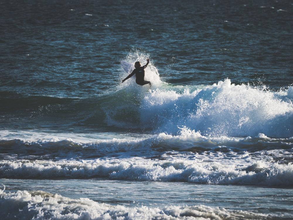 A Huntington Beach surfer slashing the surf. Shot w/ the  Olympus OM-D E-M1 MkII  +  300mm f/4 PRO  +  MC-14 Teleconverter .