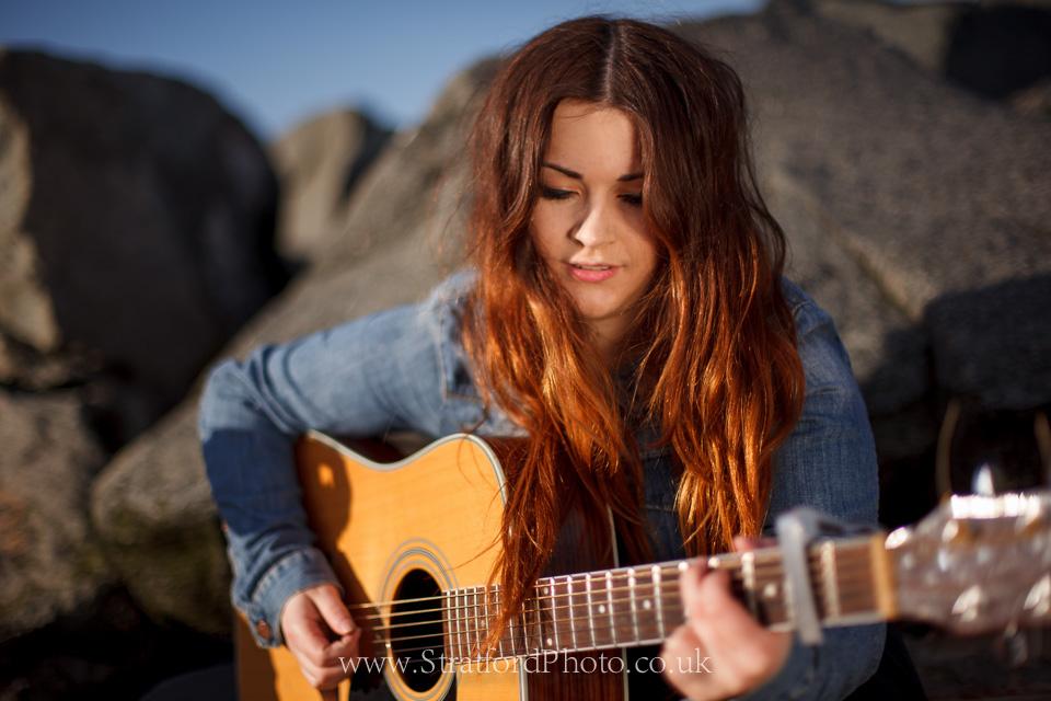 Demi McLeod plays guitar on New Brighton beach.