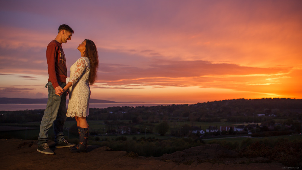 a couple stand together before a beautiful romantic sunset over thurstaston on the wirral