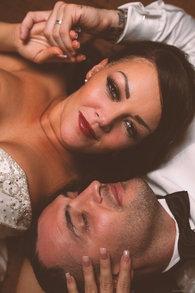 A glamourous bride and groom in black tie tuxedo lay down and share a moment together on their wedding night