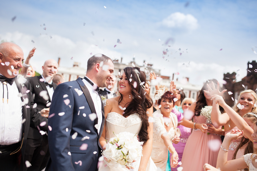 A bride and groom sharing a loving look as friends and family throw conetti at Knowsley Hall in Liverpool