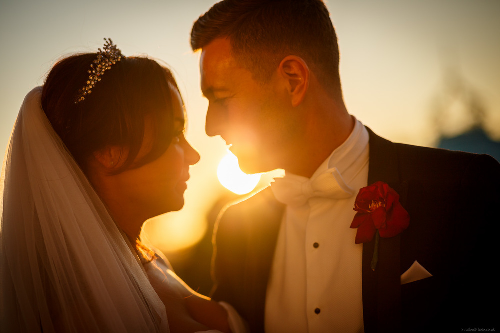 A bride and groom share an intimate moment before a setting sun at the Isla Gladstone Liverpool