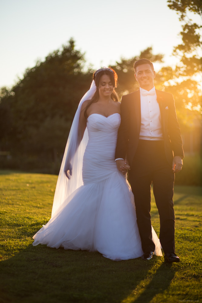 A newly married couple stroll in the grounds of the Isla Gladstone in Liverpool as the sun sets behind them filling the image with flare