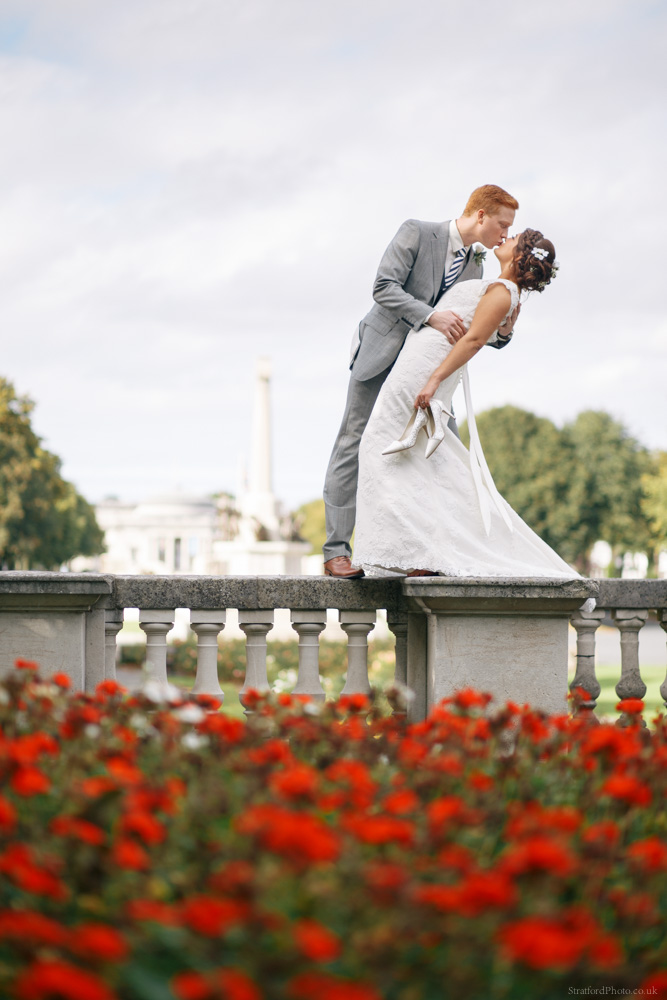 A bride and groom share a romantic kiss on the balustrade at Port Sunlight
