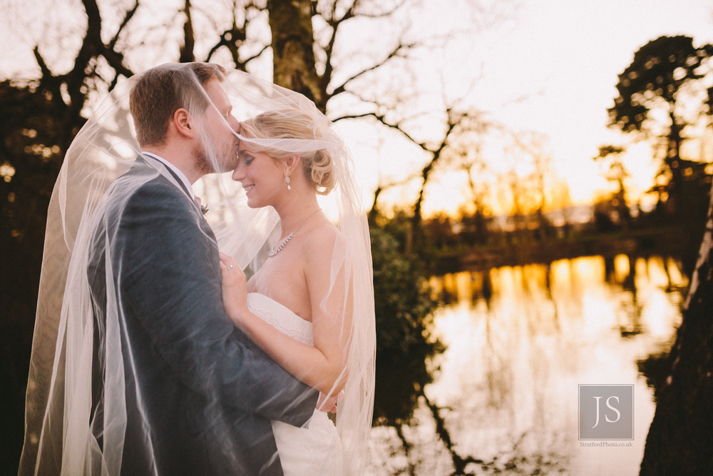 a bride and groom share a loving moment by a lake at inglewood manor on the wirral as the sun sets behind them