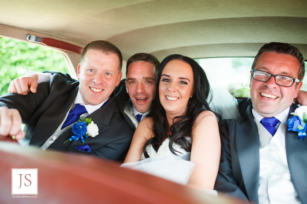 A bride and groom sqeeze into the back of their Bentley wedding car with two of their groomsmen.jpg