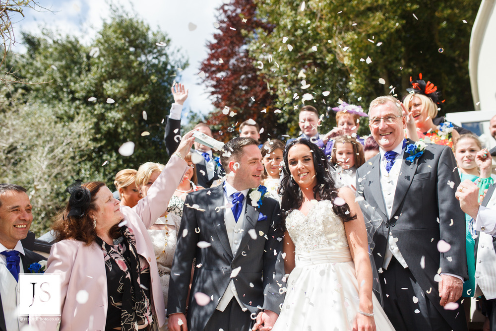 A bride and groom smile under confetti on a hot wedding day.jpg