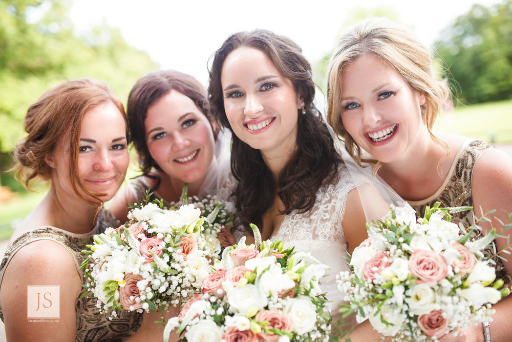 A bride with her bridesmaids smile with their posies.jpg