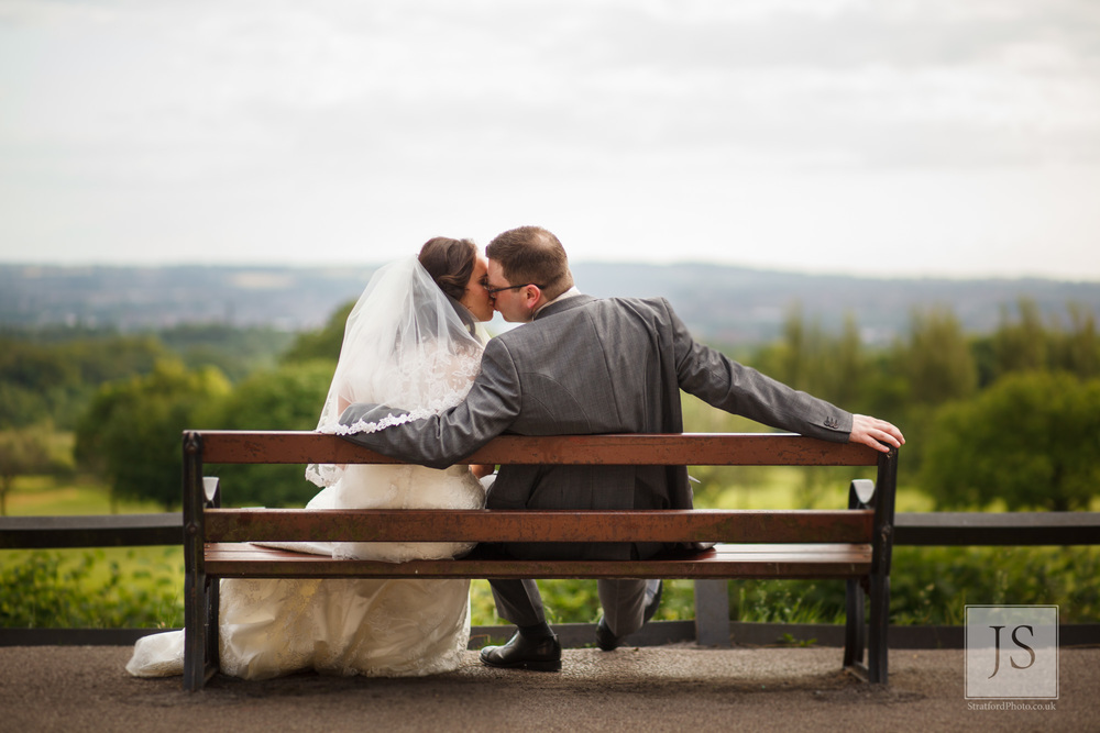 A couple kiss on a bench with the Lancashire hills in the background at Haigh Hall.jpg