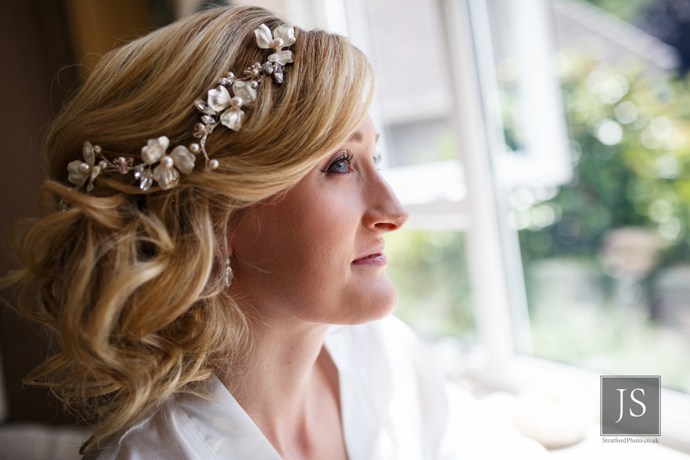 A serene bride to be waits with her hair and makeup done.jpg