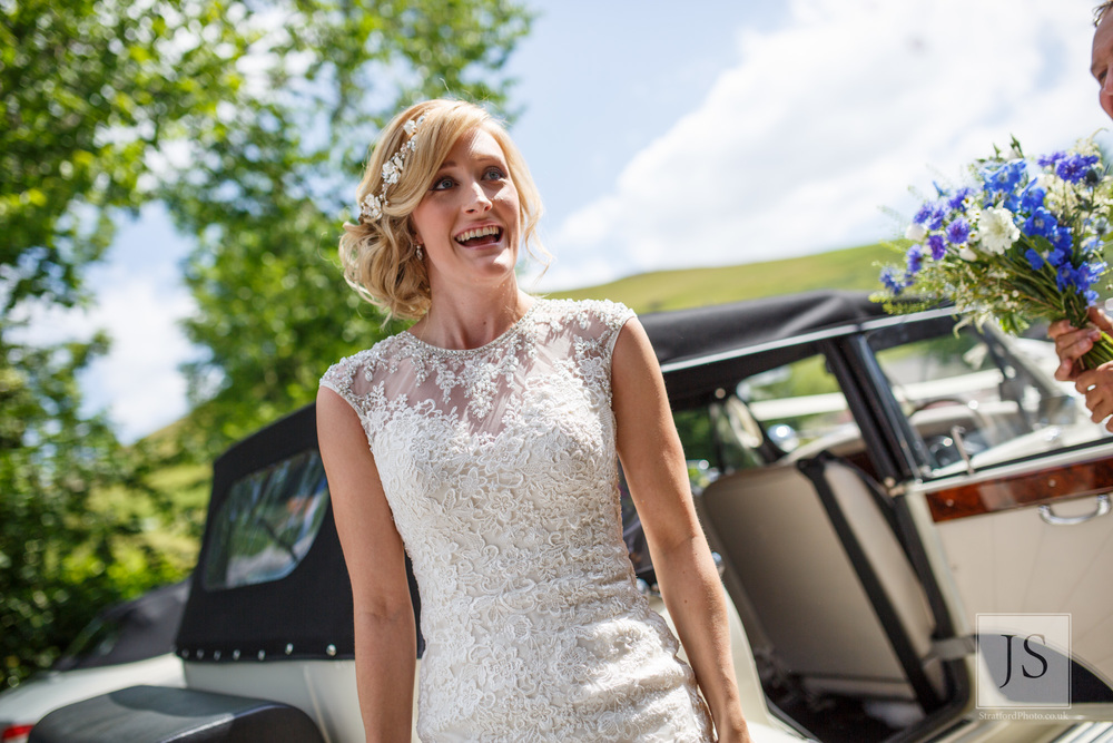 An excited brides gets out of her wedding car.jpg