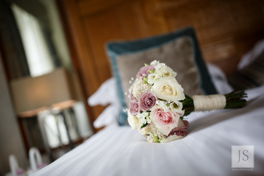 A bouquet of flowers sits on the wedding bed.jpg