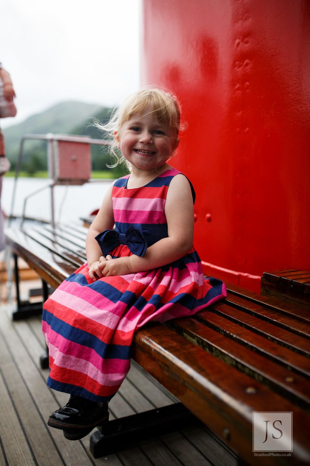 A beautiful little girl smiles at the camera on a Lake Ullswater boat.jpg