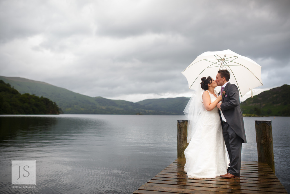 A bride and groom kiss on a jetty at Lake Ullswater.jpg