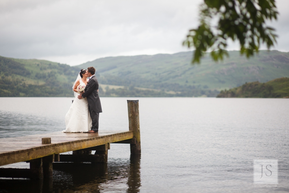 A bride and group kiss at the end of a jetty on Lake Ullswater.jpg