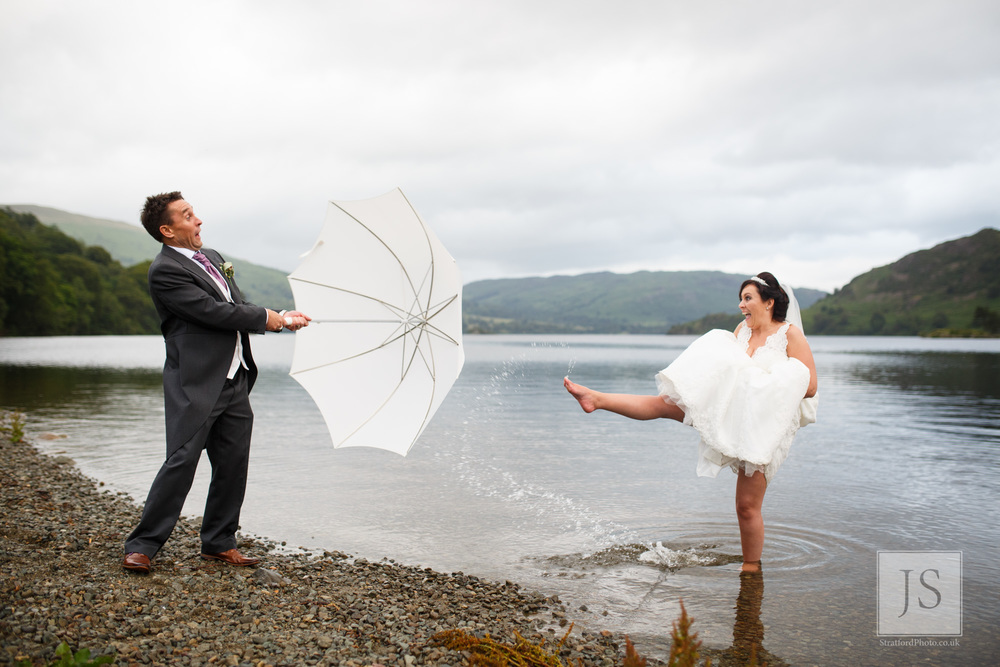 A bride kicks Lake Ullswater water at her groom as he holds up an umbrella.jpg