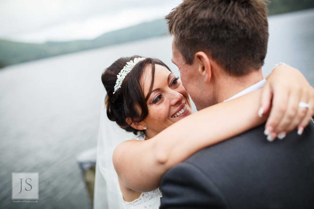 A bride smiles as she looks into her gooms eyes at Lake Ullswater.jpg