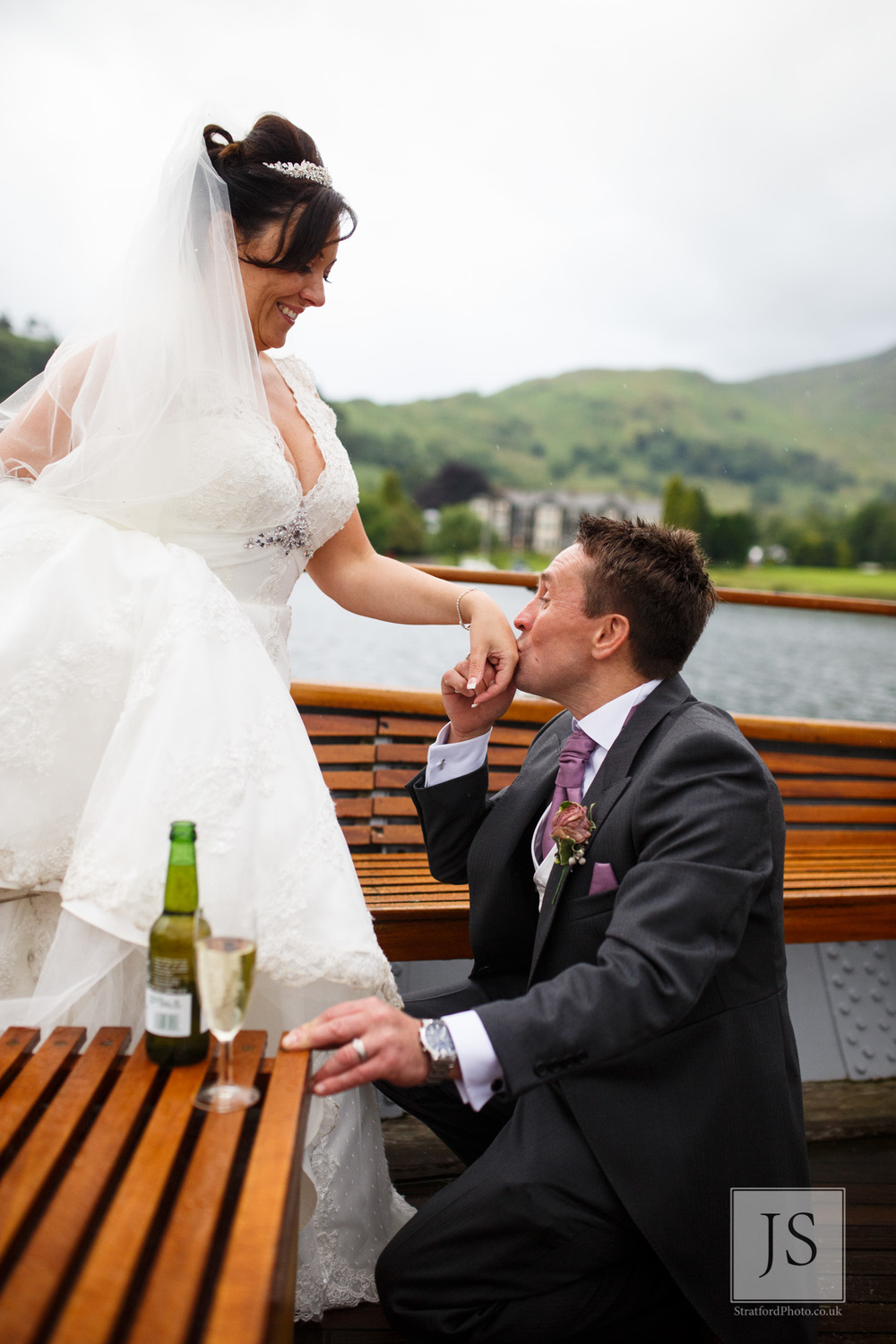 A groom kisses his brides hand at the spot where he proposed on Lake Ullswater.jpg