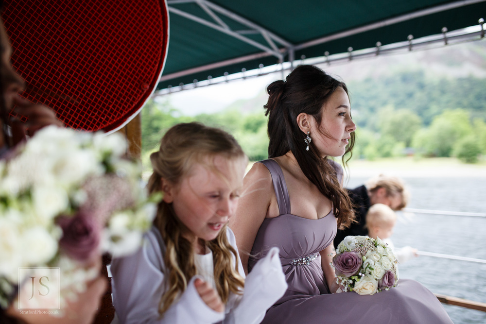 A young bridesmaid looks out over Lake Ullswater from a boat.jpg