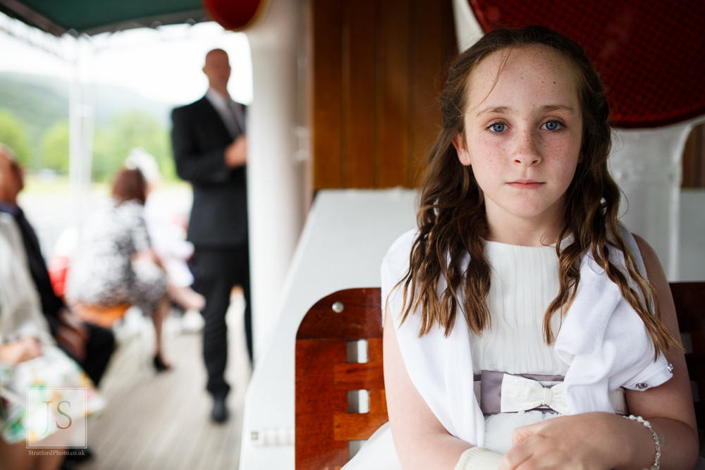 A young flower girl stares into the camera on lake Ullswater.jpg
