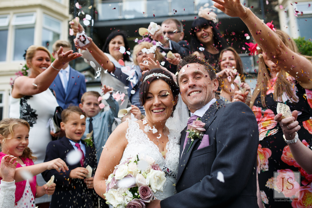 A bride and groom smile as confetti is thrown over them.jpg