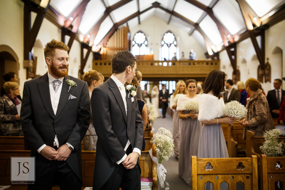A nervous groom waits for his bride to come odwn the aisle.jpg