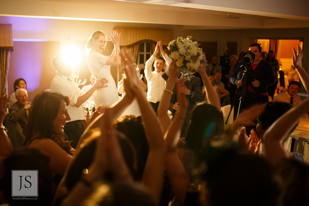 A bride throws her bouquet across the dance floor at Leasowe Castle.jpg