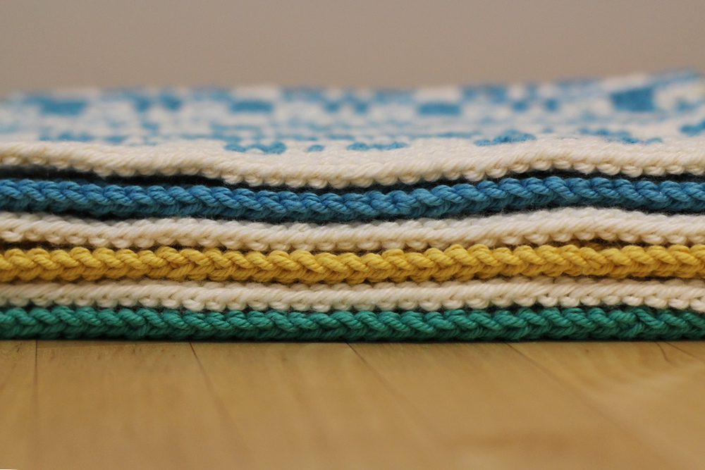 Colorful and geometric, the Mosaic Sisters are textured mosaic knit cloths perfect for the kitchen or the bathroom. Each cloth is made with garter stitch and slipped stitches that are simple to knit, but create complex patterns. All of the sisters can be made as a kitchen towel, washcloth, or coaster. Make a full set in 2 colors or mix and match.