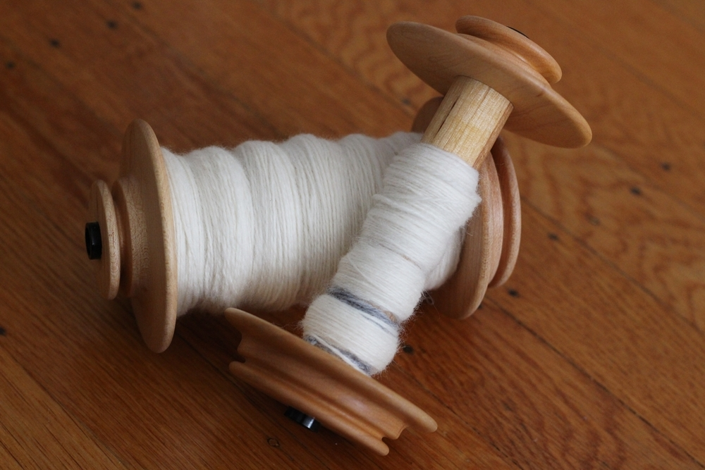One mama skein and one baby skein of plied cashmere ready to come off the bobbins.Cashmere is as soft as everyone says it is, and here's how I turned 2 oz of it into yarn.| Notes About Spinning Cashmere - withwool.com