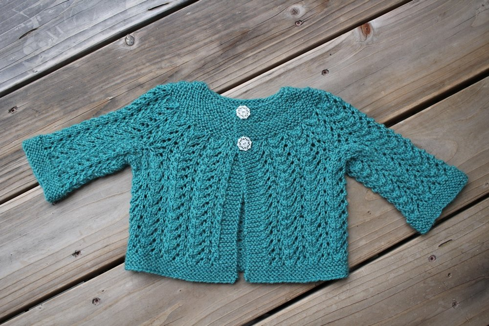 Pithy instructions, a little garter stitch, and a bunch of lace make up the famous February Baby Sweater. It's a good test of knitting skill too. | withwool.com