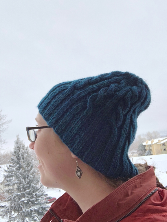 The Windbreaker hat is a ridiculously stretchy cabled hat. Quick and easy to knit, the free pattern uses less than 1 skein of worsted weight yarn and is a great gift. #knitting | withwool.com