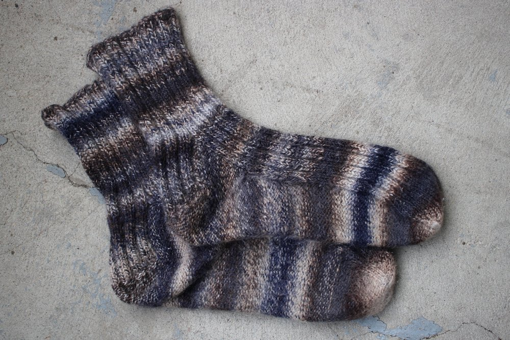 2.5 years later, this pair of 100% wool handspun socks is still going strong! No holes, thin spots, or fraying. The opposing 3-ply yarn construction makes a really durable sock yarn. #handspunyarn #tuffsocksnaturally | withwool.com