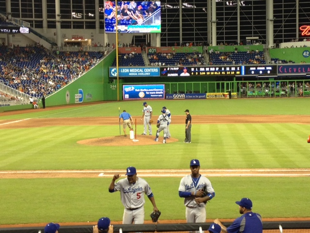 Juan Uribe and Hanley Ramirez head to the dugout while the Marlins' slow-arriving ground crew fixes an issue with the mound for closer Kenley Jansen.