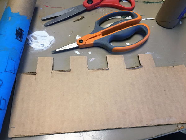 I cut out a battlement (the proper term for the tooth-and-gap architecture on a castle) from cardboard.