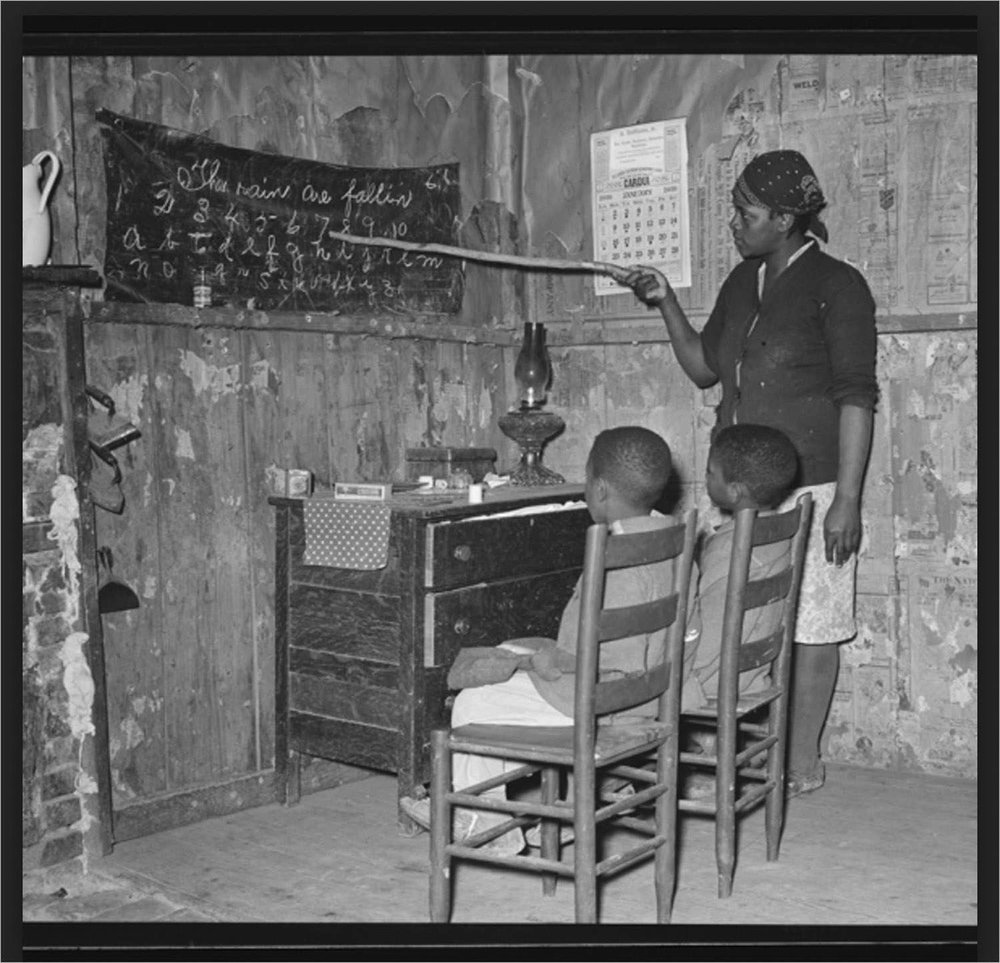 Mother teaching children numbers and alphabet in home of sharecropper. Transylvania, Louisiana
