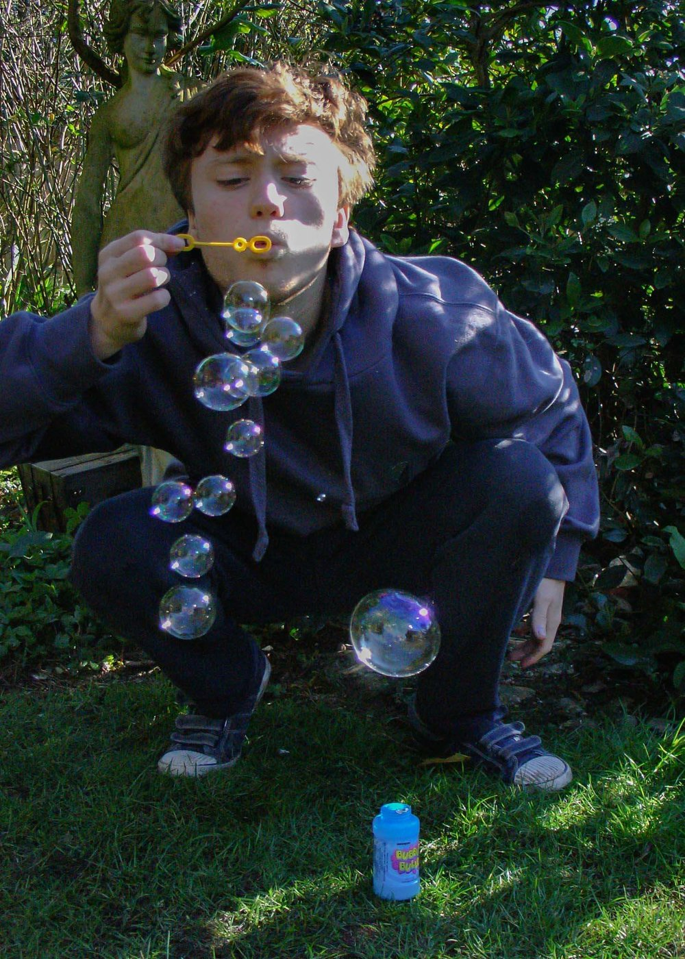 Title of Image:    Bubble day Description:  A live photo and a movement + action shot How did you take the shot? We had to make sure it shot fast we pressed the button half way to focus then we held the button all the way down once he started blowing bubbles.      When you look at the photo what do you think?      It says pop and its breath taking because you use your breath to blow bubbles but you can't see your breath, only the bubbles so that's the good thing. How hard was it to take the shot?    It was quite hard because he only blew one bubble, so we were doing it a long time to complete this task.