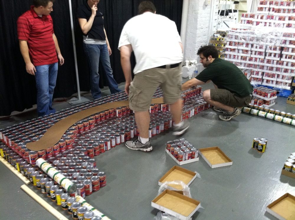 Stacking the first couple rows for the flag. In this photo, you can also see our first layer of structure to help steady the cans as we stack multiple layers on top of one another.