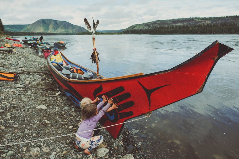 Our kids check out the dugout healing canoe on the banks of the Yukon river in Fort Selkirk during our 32 day, 900 km. family canoe expedition.