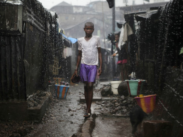 A child stands in the rain in Freetown, the capital city of Sierra Leone August 22, 2012. Source: Reuters photo by Simon Akam, used by the Council on Foreign Relations.