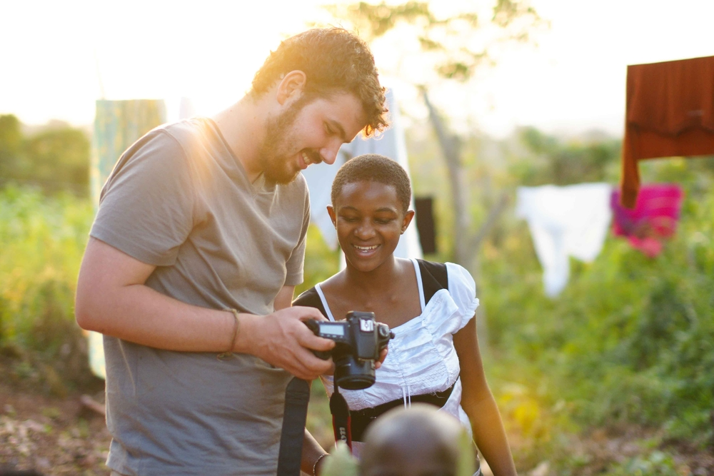 Fellow photographer Ryan Ihle shows a portrait to a child sponsored by GAAF. Uganda