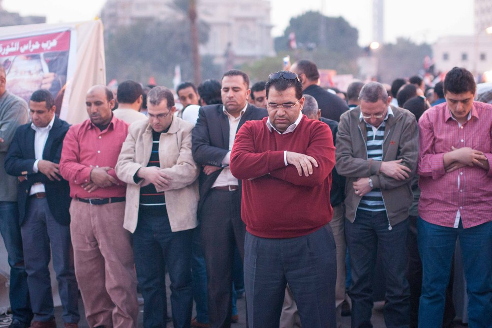 A man leads the prayer in Tahrir Square as the sun begins to set.