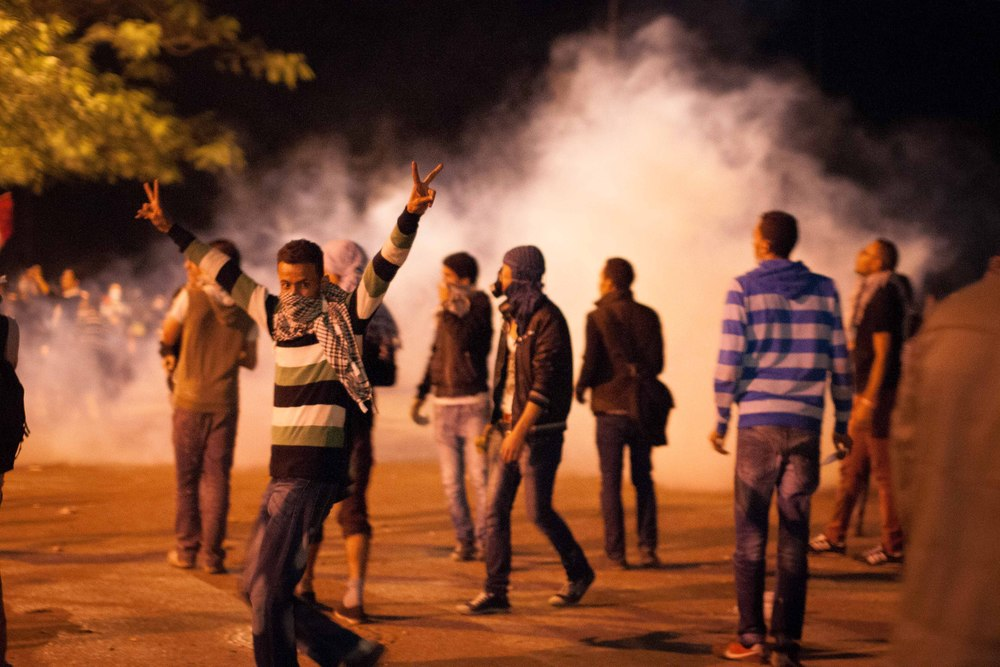 A protestor flashes the 'victory' sign as a canister is hurled back at police. Fireworks were soon shot at the police, prompting a barrage of tear gas grenades to come back.