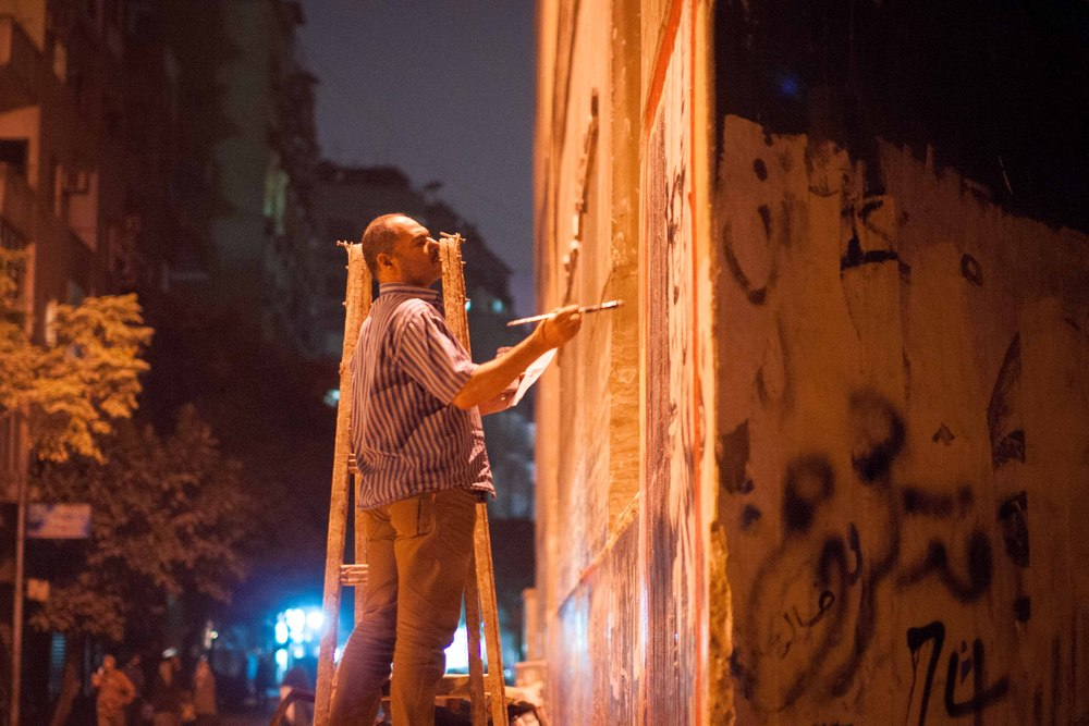 A lone artist works on his mural of famed Egyptian writer Naguib Mahfouz on Mohamed Mahmoud Street.