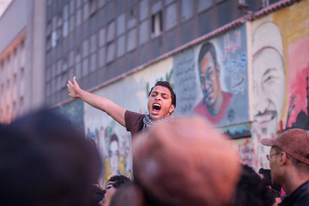 Chants agains the government and Morsi are framed against the graffiti of Mohamed Mahmoud Street. The murals depict those who died during the clashes last year.