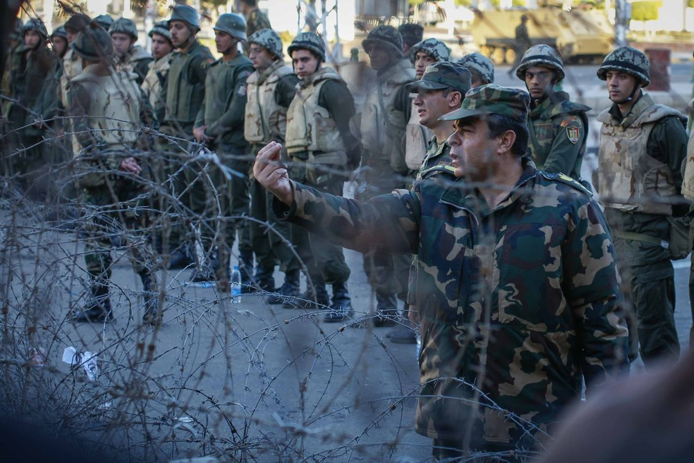 A member of the Egyptian military gestures with the sign to 'Wait!' at protestors. Protestors and the military exchanged heated words (at times) through the barbed wire.