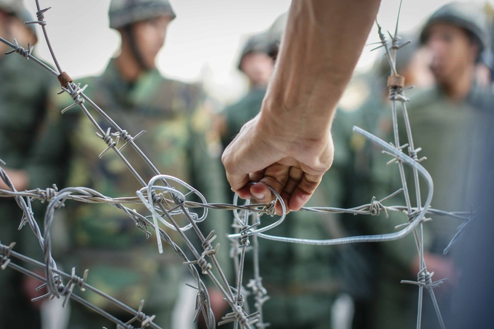 A hand reaches over to untie the wire holding the barbed wire together. More and more protestors climbed atop the barricade to dismantle the wire. Many people complained about the wire, demanding it go so they could protest in front of the palace.