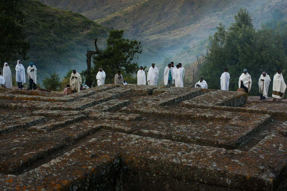 Perched high in the mountains of Northern Ethiopia, the small town of Lalibela is a place of pilgrimage during the time of Orthodox Christmas, and Ethiopian Christianity's second holiest site. Wrapped in shrouds of early morning mist and cotton, Ethiopian Orthodox Christians stand in prayer at the edge of Bet Giyorgis, the rock church carved to resemble a cross.