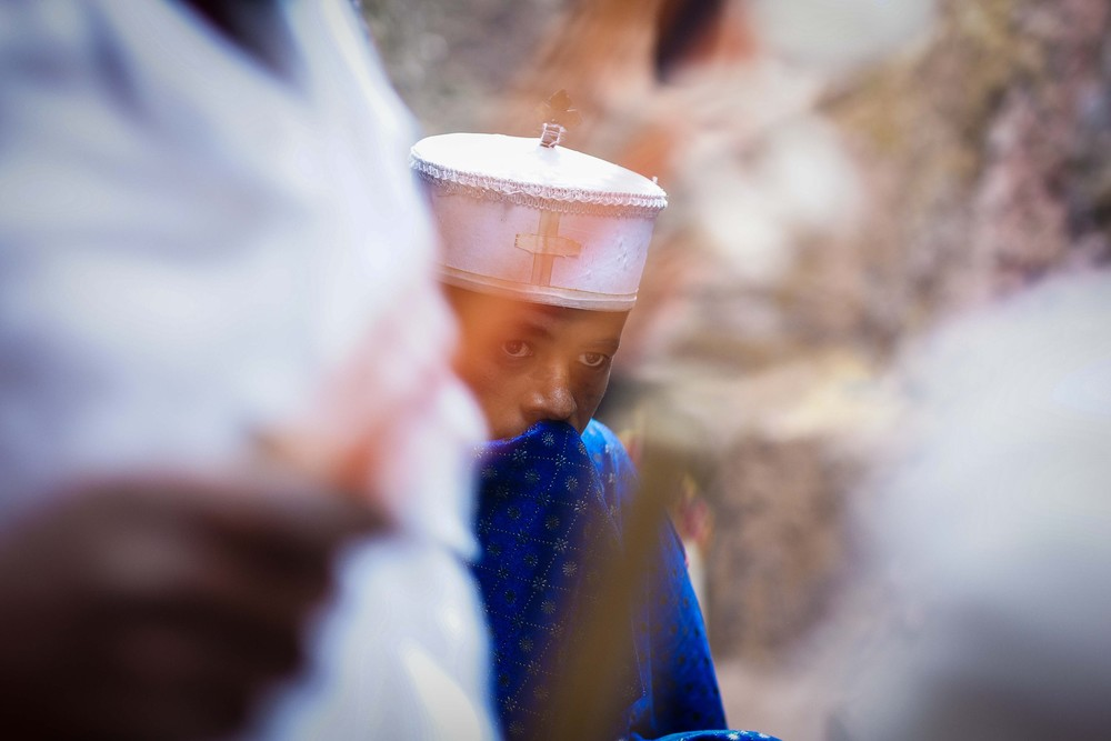 Wax candles are brought past a young priest at Bet Giyorgis.