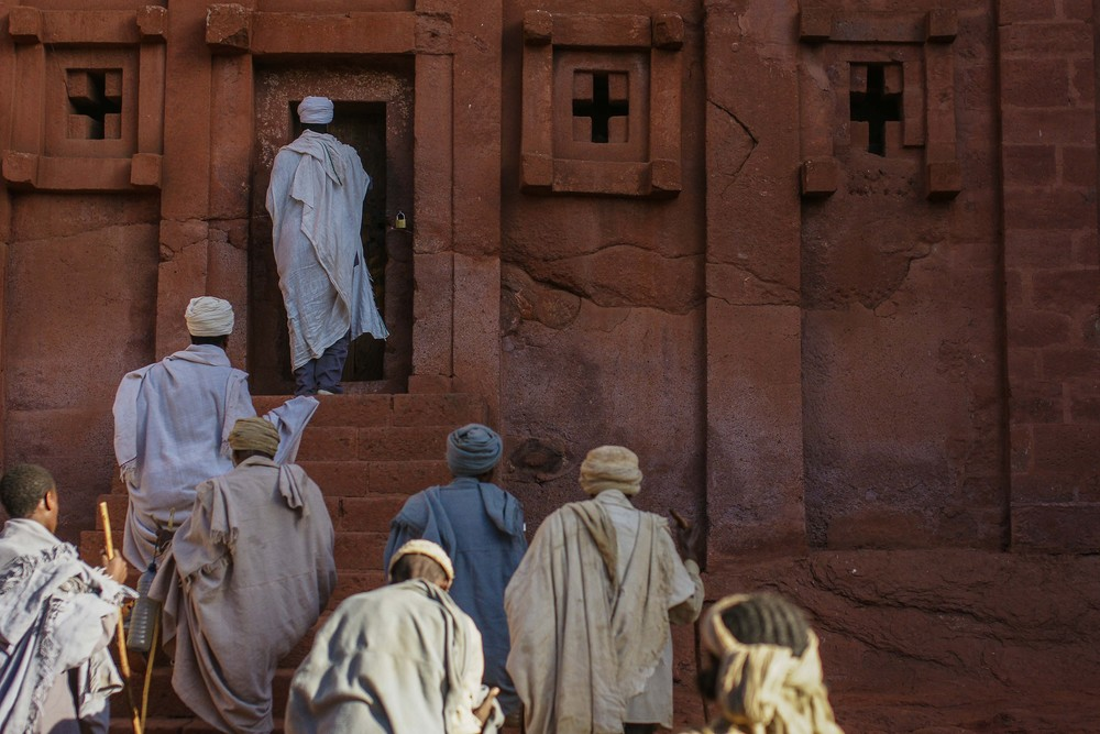 A priest leads pilgrims into one of Lalibela's 11 churches.