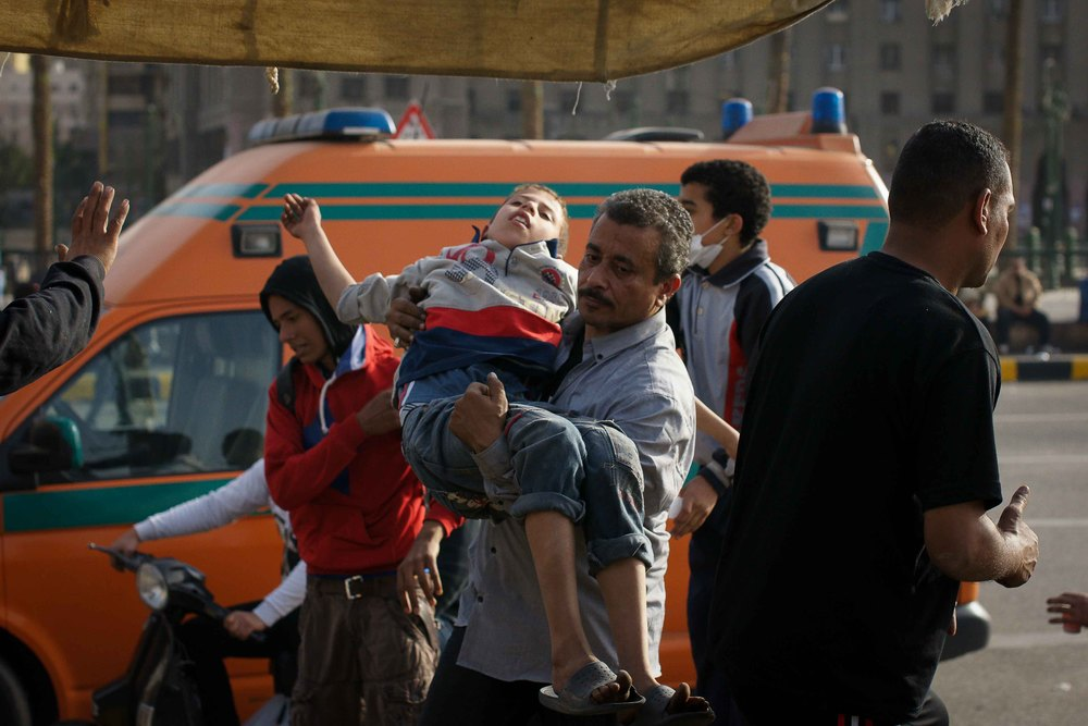 A young boy is carried into the field hospital, after being overcome by teargas.